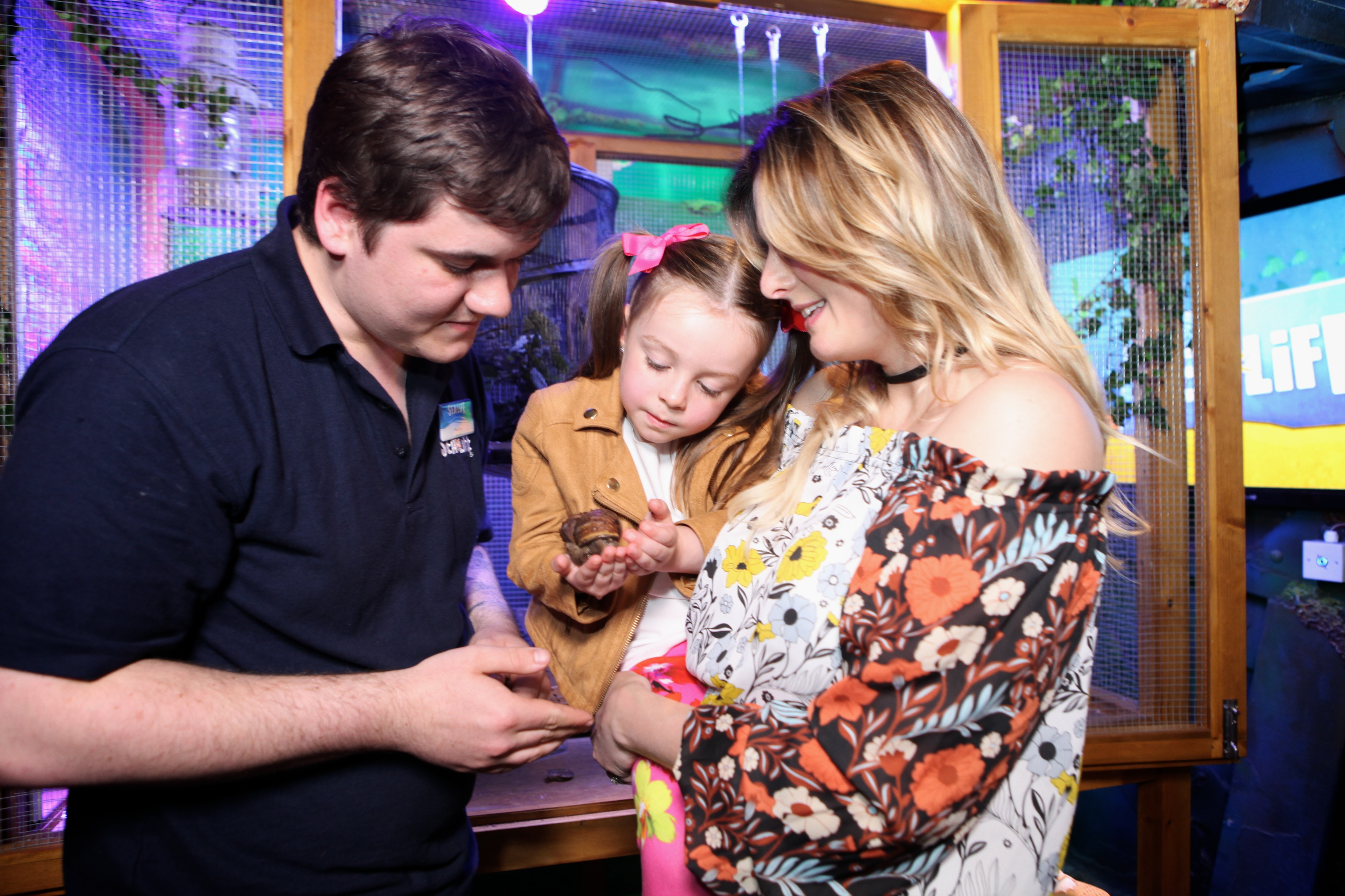 Guests with a rainforest ranger holding a snail at SEA LIFE